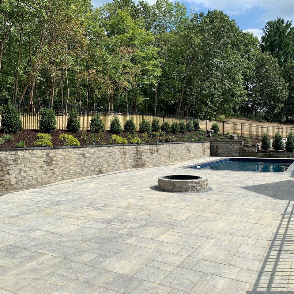 Professional Residential Masons Craft Customized Retreats For over 18 years, Landwork Contractors has been crafting personalized patios in Westchester, Putnam, and Dutchess Counties. We know the best techniques and use only top quality products with Unilock pavers for your customized projects. Our patios will turn your backyard into a beautiful retreat for your friends and family. How? Take a look at these benefits and you'll see why it's time to start planning your Unilock Patio. Create More Space for More Fun!- If your family is tired of Netflix or staring at a screen, try some outdoor time. With the right additions, a new patio can add extra space to your home. You could entertain your friends or simply spend time with family. Summer parties, holiday celebrations, and after work swims can become a part of your everyday life when you add a pool patio. Design a Safe and Relaxing Space for Your Family- The Hudson River Valley region is known for its beautiful valleys and rocky ground. While these views are stunning, their uneven pathways can be hazardous. A carefully designed retaining wall in your pool patio can help tame the terrain and provide calm, safe areas for your family to relax. Add in a walkway with slip-resistant pavers and you'll have a gorgeous space that puts safety first without sacrificing style. Add Beautiful Views- An outdoor space doesn't have to be bare to be beautiful. The right pool patio design can be artistic and useful. Imagine looking out your window at a lush landscape with flowering trees and ornamental shrubs highlighting flagstone pavers and beautiful blue waters. Every day can feel like a spa getaway with the right design. Increase the Value of Your Home- Hardscaping features are one of the top ways to increase home values. Pool patios never lose their worth in any home market. When you choose to add a patio, you are setting your home apart from all the others. Use professional masons and you'll attract attention and get more out of your investment. A Million Options for Customized Designs- You don't have to have a cookie-cutter version of the most popular design. Unilock pavers come in so many different styles with so many different options, you can create something beautiful and totally unique. Prepare for Summer Now with Patio Designs Summer may seem months away but it will get here before you know. Get ready for summer parties and celebrations by planning your patio design now. Call our experts at 914-479-2537 or make an appointment online. We'll have you relaxing by the pool in no time.